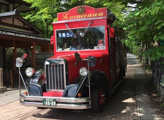 軽井沢を走る赤い観光バスの画像です