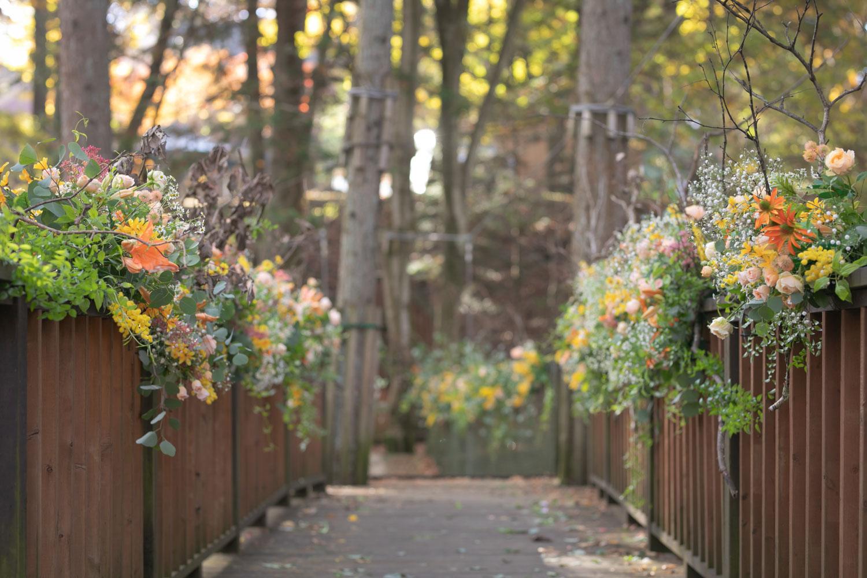 挙式会場に向かう吊り橋が花々で彩られている写真です